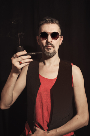Portrait of a man smoking a pipe on a black background Imagens