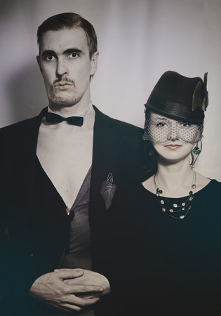 Young couple theater actors in a retro style on a light background. Vintage photo