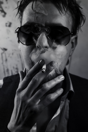 Portrait of a smoking bearded man dressed in sunglasses