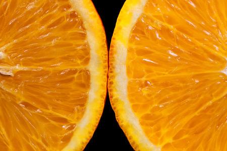Two slices of orange on a black background macro