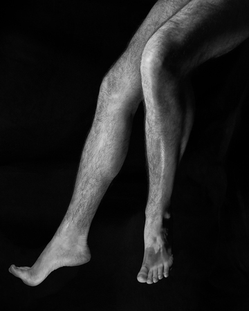 Beautiful, muscular, bare male feet on a black background. Classic high-contrast art photo photo