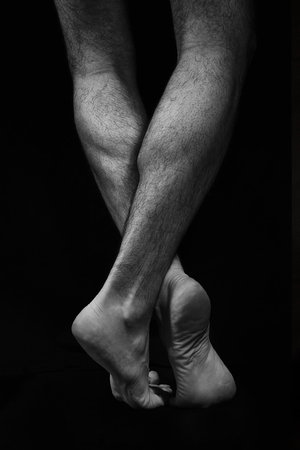 Naked muscular male legs on a black background. Contrast black and white photo Imagens