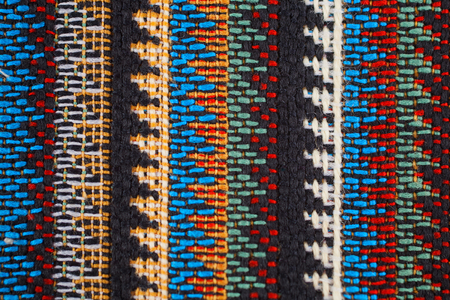 Texture of  fabric with  traditional Mexican pattern macro. A tissue sample