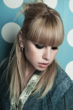 Young beautiful blonde girl with long hair. Studio portrait on a blue background with white circles Imagens
