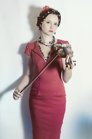 Young violinist woman with violin in hands on a white background. Studio portrait