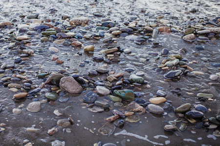 Wet pebbles and sand on the seashore