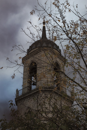 Bell tower of the old Christian cathedral against  a dark autumn sky.