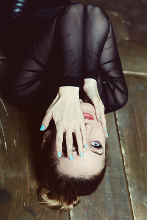 Young beautiful woman lies on the floor, covering  face with her hands photo