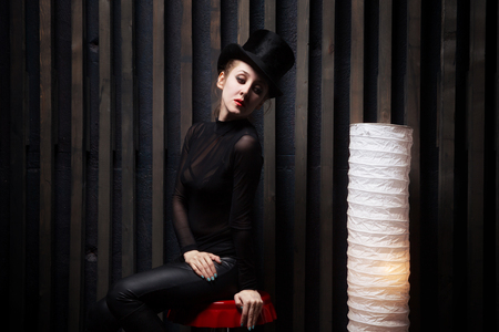 Beautiful young woman wearing  top hat Sits on  chair near to a floor lamp in a dark room Imagens