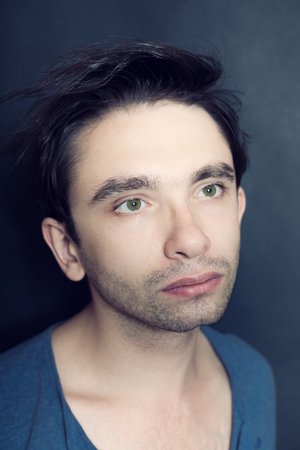 Portrait of  young green-eyed man with bristles on his face. Studio photo on  black background Imagens