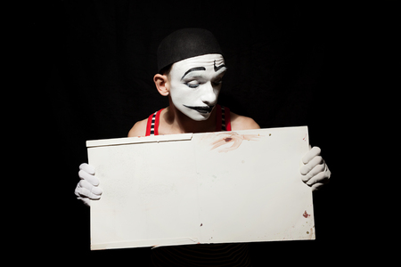 Portrait of sad mime holding white paper dirty sheet in hands.  Studio photo on a black background photo