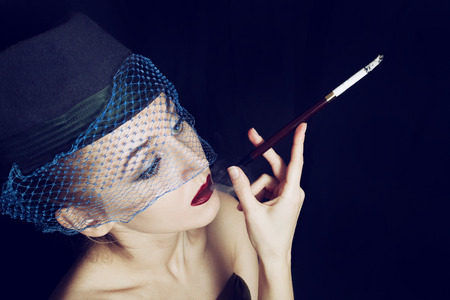 Portrait of a young beautiful woman dressed in a hat with a veil smoking a cigarette. Photo in retro style on a black background Imagens