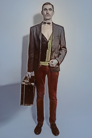 Studio portrait of Theater actor holds a suitcase in his hand Imagens
