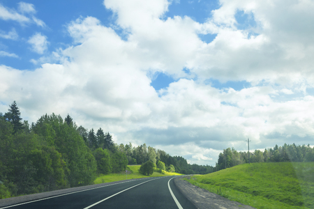 Landscape with an asphalt road in a sunny summer day Imagens