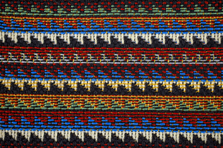 The texture of fabric with traditional Mexican pattern macro.