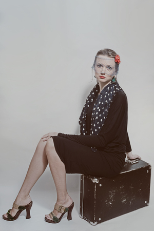 Young beautiful woman in retro style sitting on an old suitcase