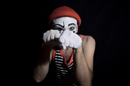 Portrait of fighting mime on a black background