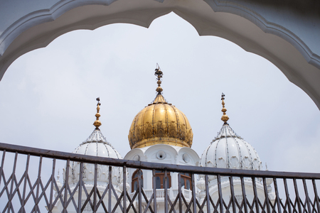 White and golden domes of mosques against the cloudy sky background Imagens