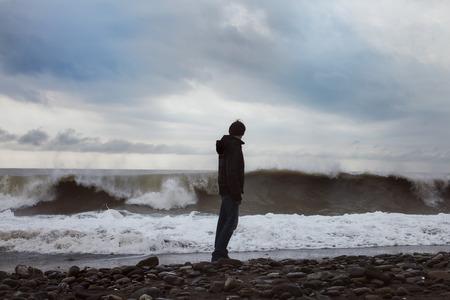 Młody człowiek stojący na brzegu morza