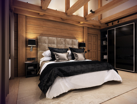 The cozy bedroom is in the attic of a chalet. Huge bed with numerous pillows is dominates the room. The interior is decorated with wood and natural materials.