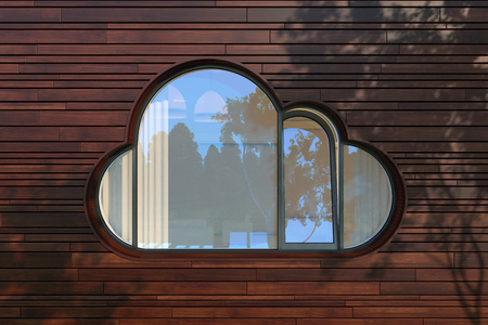 cloud icon: The window like a cloud icon on modern wood planks fasad. The rays of the evening sun through the trees and are left on the wall of a fantastic picture branches and leaves of the crown. Stock Photo