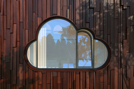 balk: The window like a cloud icon on modern wood planks fasad. The rays of the evening sun through the trees and are left on the wall of a fantastic picture branches and leaves of the crown. Stock Photo