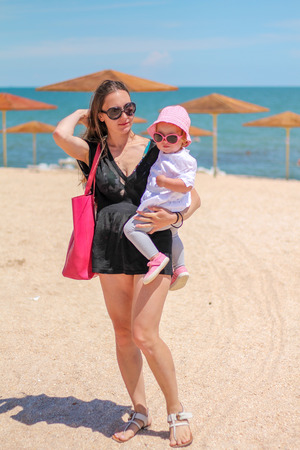 hot day: Little baby girl with mother playing on the beach near the sea on a hot day during the summer holidays