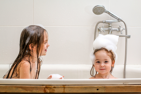 Two little sisters play in a bath with foam. They are very cheerful and lovely. Banco de Imagens - 96675731