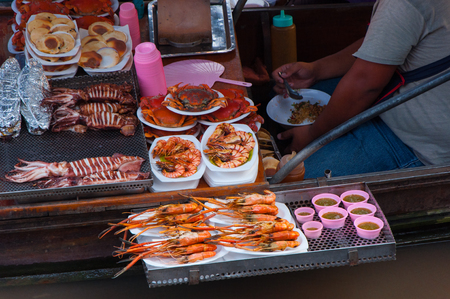 shrimp boat: grilled Shrimp, crab and squid on boat for traveller at Amphawa Floating Market Stock Photo