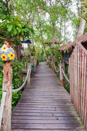 hand rail: timber path walkway bridge with rope hand rail in resort