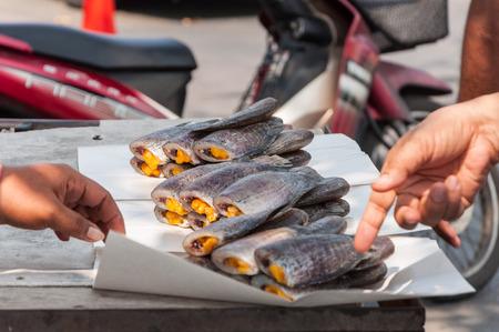 pectoralis: buying dry gourami fish pile on paper - hand closeup Stock Photo