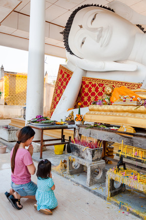 glorify: Nonthaburi, Thailand-February 19, 2016 : mother and daughter pay respect to sleeping buddha statue Editorial