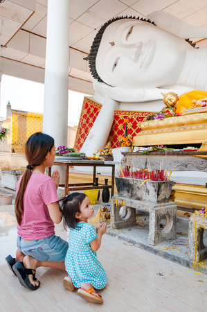 venerate: Nonthaburi, Thailand-February 19, 2016 : mother and daughter pay respect to sleeping buddha statue Editorial