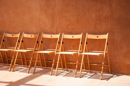 the sun and shade: empty wooden chairs against orange cement wall with sun shade
