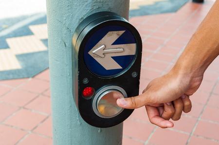 pulsando sobre el botón de color Negro peatón cruce la mano para cruzar la calle. Foto de archivo