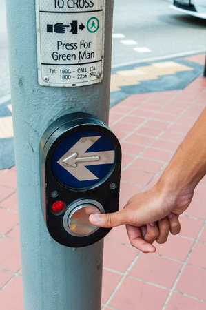 hand pressing on Black color pedestrian cross button to cross the road.