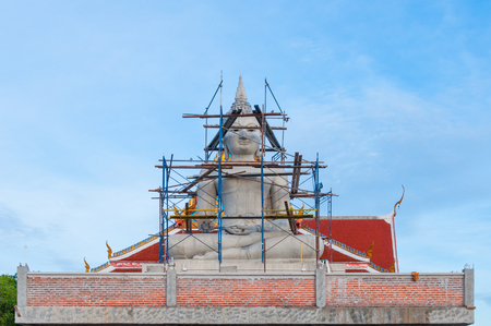Big statue of Buddha under construction with blue sky in background Stock Photo