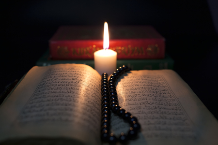 Quran books are illuminated by candle.