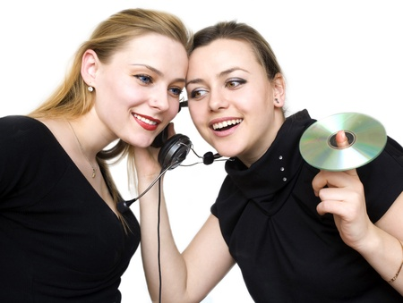 two girls attentively listen sounds from headsets photo