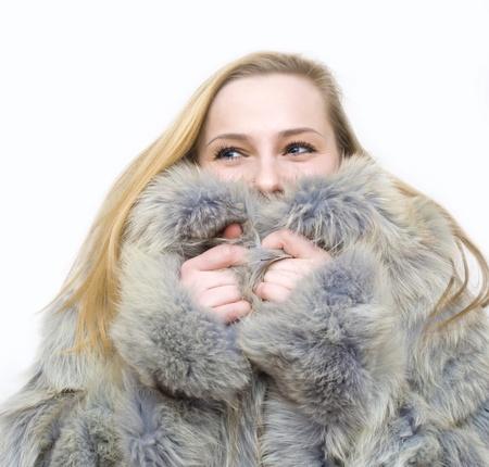 bontjas: een meisje in een bontjas door een koude winter houdt een vlinder Stockfoto