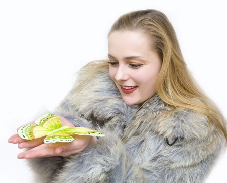 a girl in a fur coat by a cold winter holds a butterfly Stock Photo - 9341406