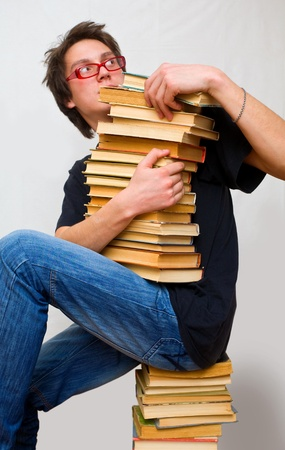 a student in horror holds a mountain of their textbooks photo