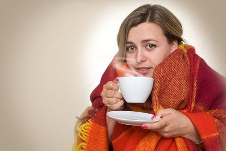 A young woman caught a cold, wrapped in a blanket and something hot drink from a cup. Stock Photo - 10841476