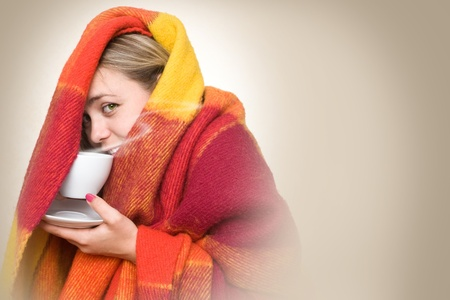 freezing: A young woman caught a cold, wrapped in a blanket and something hot drink from a cup.