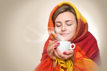 gripe: Una mujer joven cogió un frío, envuelto en una manta y beber algo caliente en una taza. Foto de archivo
