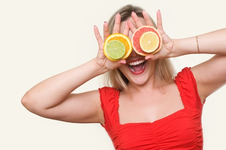 beautiful blond girl using citrus as glasses and smiling photo