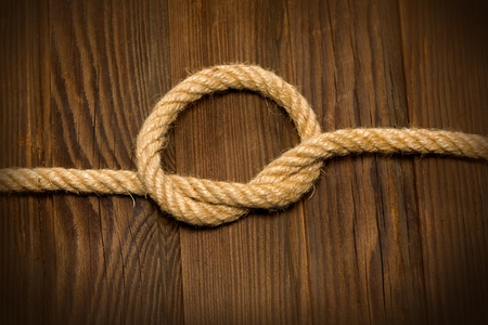 lashing: knot of the rope on the weathered wood background Stock Photo