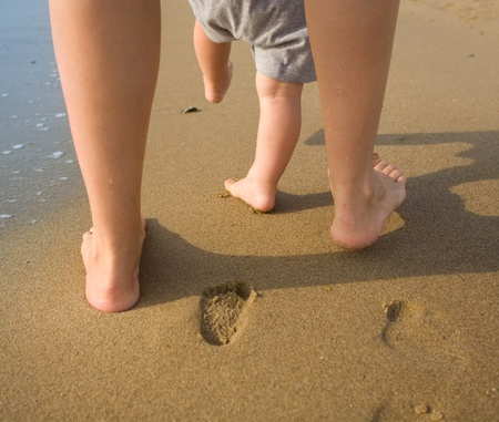 big toe: mom helps to make the childs first steps on the beach