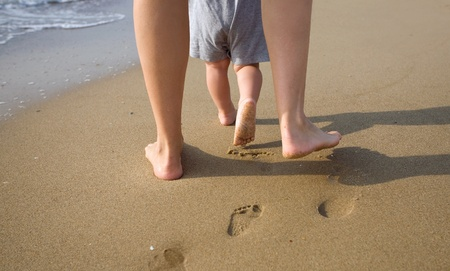 feet in sand: mom helps to make the childs first steps on the beach