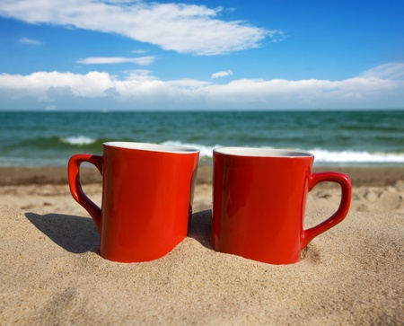 liquid summer: two red cups on a sunny beach